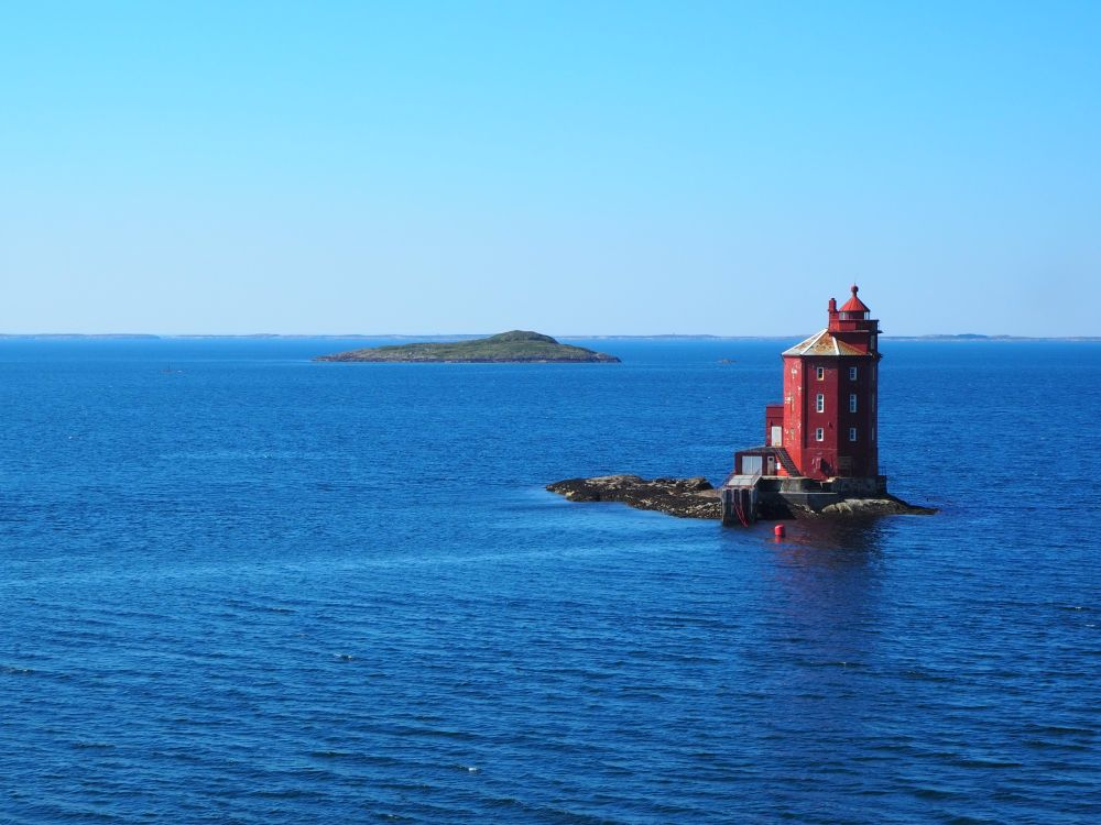 A red lighthouse on a very small, rocky bit of land, surrounded by blue sea, with another rocky island in the background.
