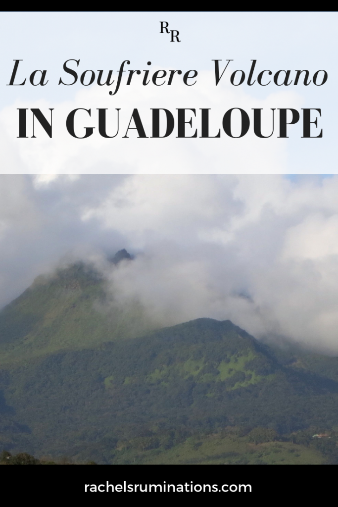 Pinnable image Text: La Soufriere Volcano in Guadeloupe Image: the green sides of the mountain, topped with clouds.