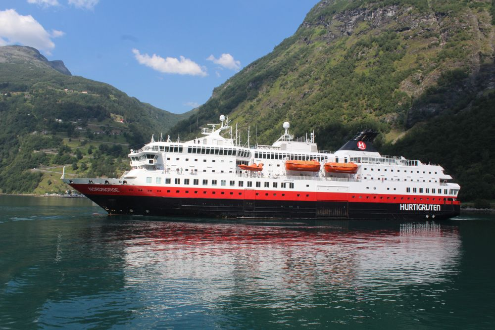a view of the MS Nordnorge from the side. Painted white on the top four or five levels, with one level below that painted red, and black below that for the hull. Orange life boats hang on the side. Mountains in the background.