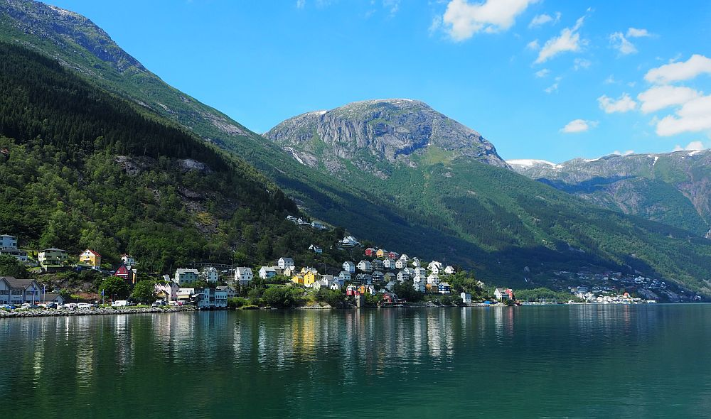 In Oddo, Norway, a cluster of colorful houses stand on the shore of a lake, backed by mountains.