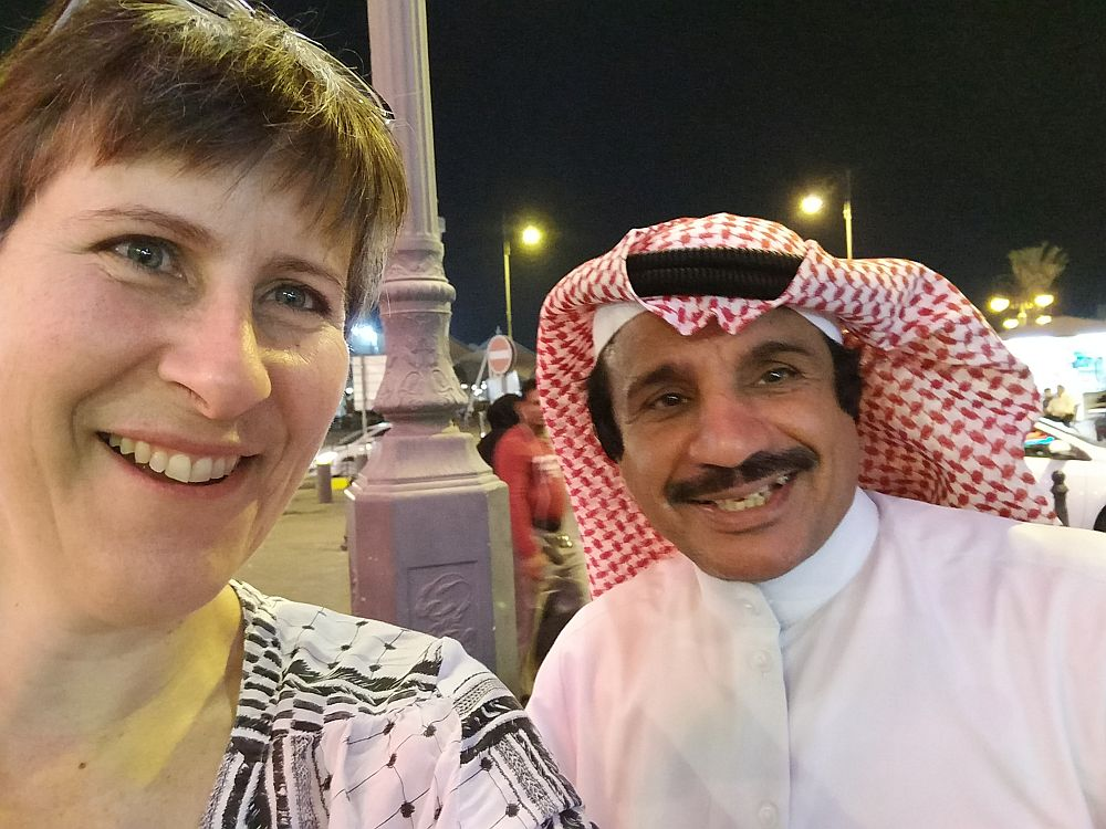 A picture of Rachel with Naawaf Al Shammari, a famous Kuwaiti actor, in the Kuwait market. He is wearing a traditional red and white headdress.