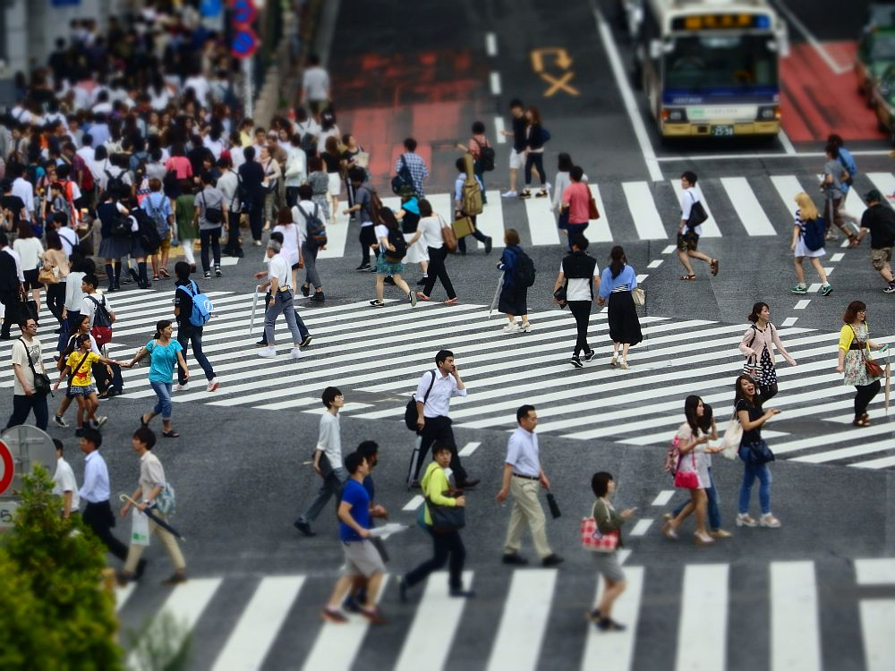 Shibuya crossing in Tokyo has multiple white-striped crosswalks (connectiing all four corners plus two diagonals. Lots of people are busy walking across, though many are not in the crosswalks.