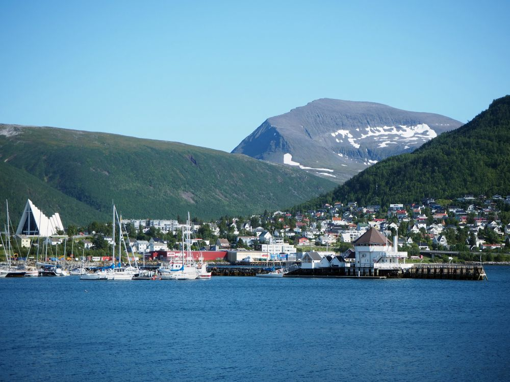 A cluster of buildings, with a large, modern church on the left and sailboats moored in front. Behind, two green hills and then, behind them, a higher hill with snow in patches on its side.