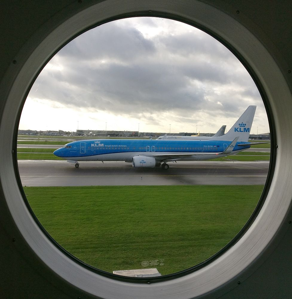 A round airplane window frames a passing blue and white KLM jet on a nearby runway.