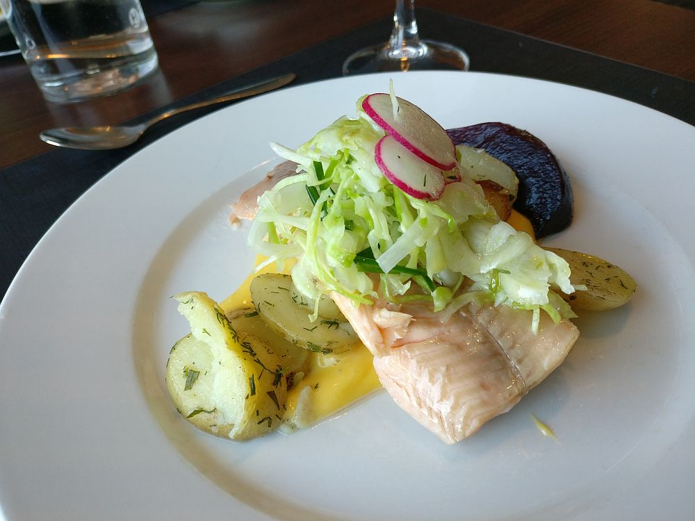The food is presented in a pile on a white place: first the hollandaise sauce underneath, then dill potatoes are visible on either side, under a piece of light-pink fish, which in turn has a small amount of shredded cabbage and sliced radish on top. The beet is only partly visible behind the fish.