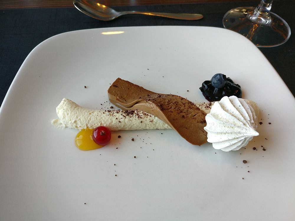 A white cream lies horizontally in a line across the plate. A piece of chocolate mousse lies across that. On the side are a bit of blueberry compote, a white meringue, and a red berry (lingonberry?) on a dab of yellow sauce.