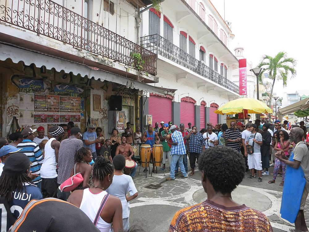On a city street, closed storefronts on the left of the picture, with lacy iron railings above, the drummer sit under the balcony. One man is shirtless and sitting, while several others are standing and playing various drums. A crowd stands/dances in a circle around them. Judging by their dark skin, these are all locals.  10 reasons people get addicted to travel.