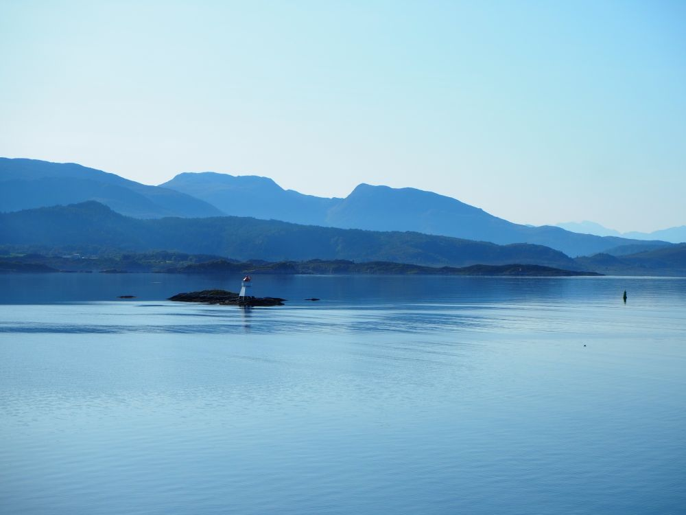 Smooth blue water. A small rock with a marker buoy on it. Behind that, rows of mountains, one behind the other. All seem blue, but darker blue in front shading to lighter blue behind.