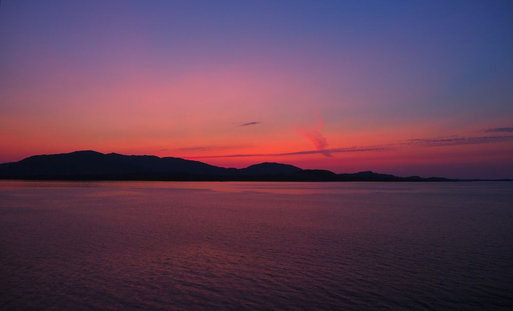 A pink and purple sunset over distant low hills, water in the foreground, very calm, reflecting the purple.