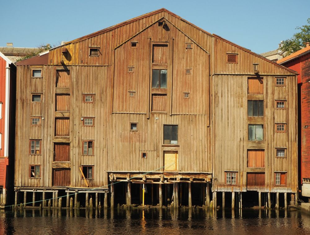 This warehouse is brown wood and looks quite massive from this vantage: 6 or 7 floors, and resting on pillars. Beams stick out above the bigger windows/doors that must have been used in the past to lift cargo from boats into the warehouse.
