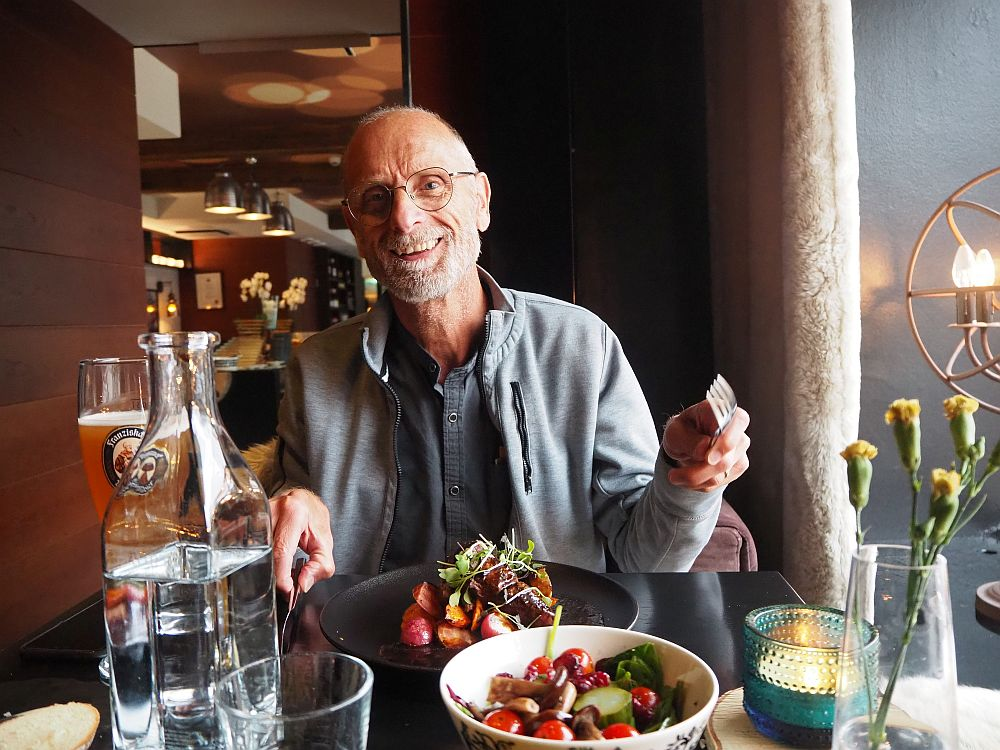 Albert, wearing a gray sweatshirt, smiles at the camera, holding his fork in one hand. In front of him is a dark brown plate with a pile of vegetables and meat in the center. In the foreground, a white bowl with salad.