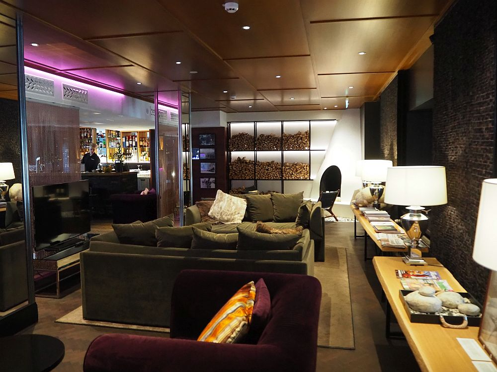 Dark, soft-looking sofas fill the center of the room, and wooden tables on the side hold magazines and lamps. In the background a bar is visible on the left, and a fireplace and stacks of wood on the right.