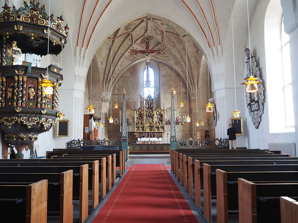 Looking down the red-carpeted aisle of the church in Gammelstad church town, rows of pews are visible on either side. At the end of the building is the altar topped with an elaborate altarpiece. A window lets light in above the altar. ON the left, an elaborate-carved pulpit is visible.