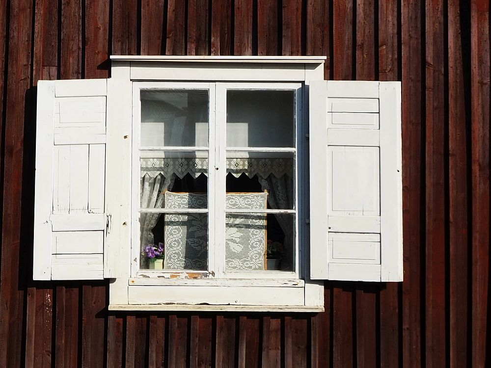 A detail photo of a window in Gammelstad church town. It has 6 panes in two columns of 3 rows. Trimmed in white, white shutters stand open on either side, bright against the dark red wall. Lacy curtains are visible within, along with some sort of white embroidered piece.