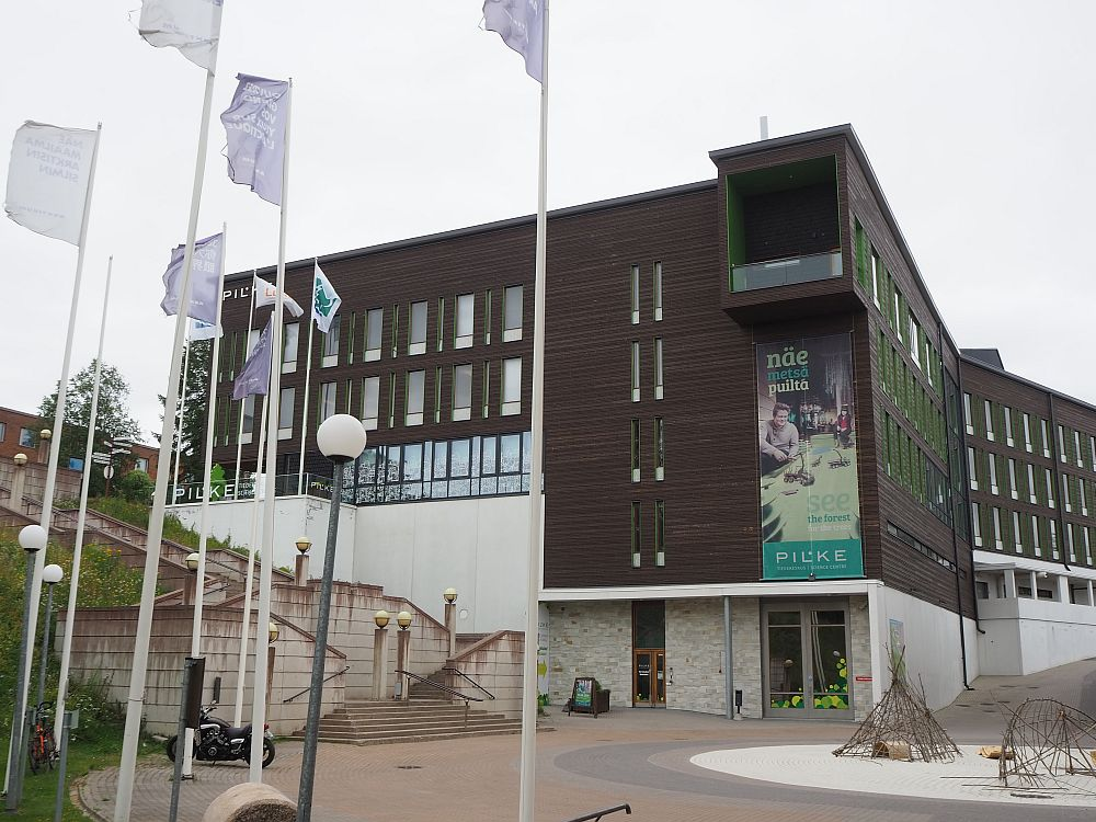 Among the things to do in Rovaniemi is to visit Pilke science center. The building is large and modern and partly built into a hill on the left. The bottom story is white, while the 4 floors above are dark brown. A piece of the top floor extends out over the entrance: a little porch, I think.