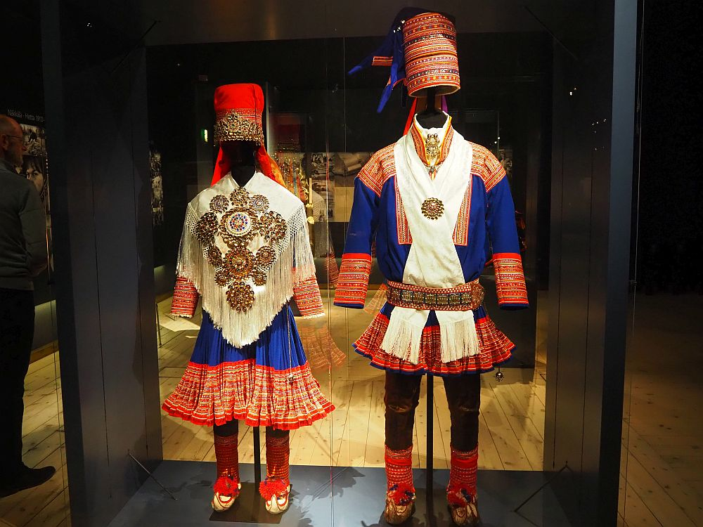Among the things to do in Rovaniemi is to visit Arktikum. On the right is a woman's outfit, with blue and red embroidered skirt, red tights, a white, very decorated poncho with fringes, and a conical red hat. The mans outfit next to it is in the same colors, but with dark, close-fitting pants and a shorter skirt. Instead of a poncho, a white scarf is around the neck and tucked into a highly decorated belt. The hat is also conical, but more richly embroidered than the woman's hat.