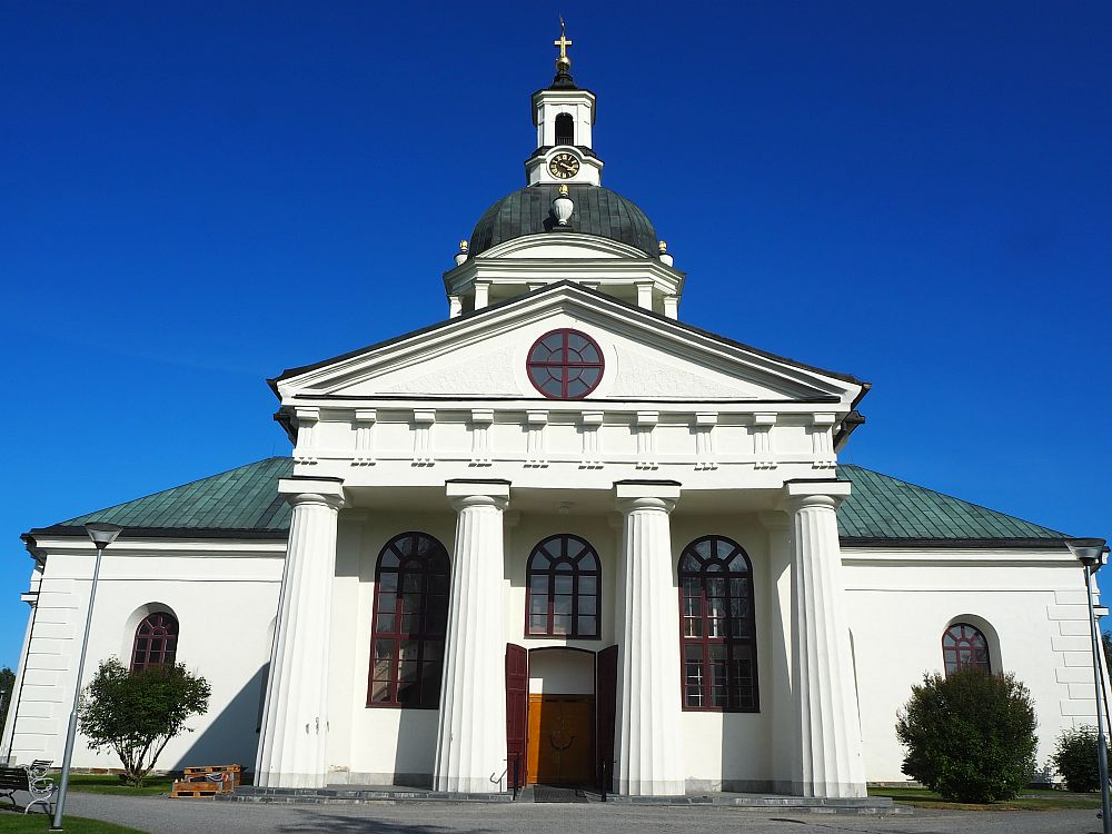 The church has a portico with four very large columns in neoclassical style. The pediment is simple, with a round window in its peak. Above the portico, part of the domed tower is visible: a grey-roofed dome, with a small white steeple on top. A clock is at the base of the steeple and a cross at the top.