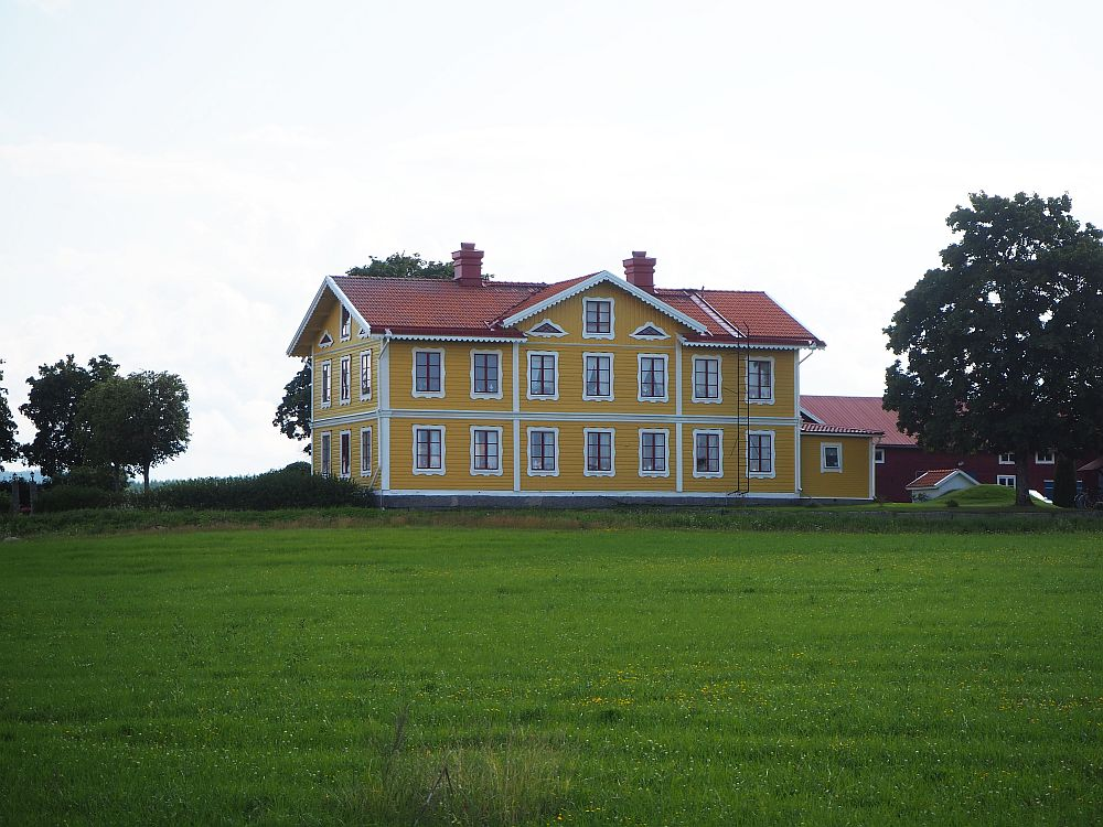 In the foreground, a green field of grass. In the center beyond the filed, a large rectangular house, painted yellow with white trim around the windows. Two stories, with smaller windows under the roof as well.