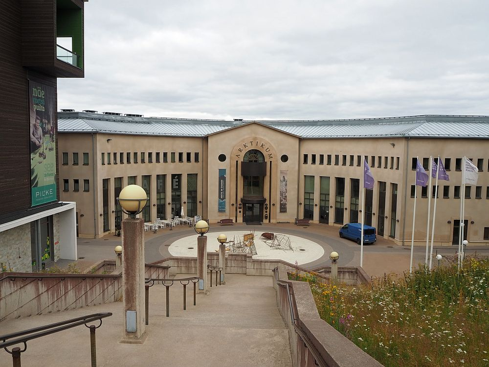 Among the things to do in Rovaniemi is to visit Arktikum. As seen from up a long staircase, the Arkticum building has an arched central entrance with a wing on either side. The building is a light pinkish brown color, and has high, multi-story windows.