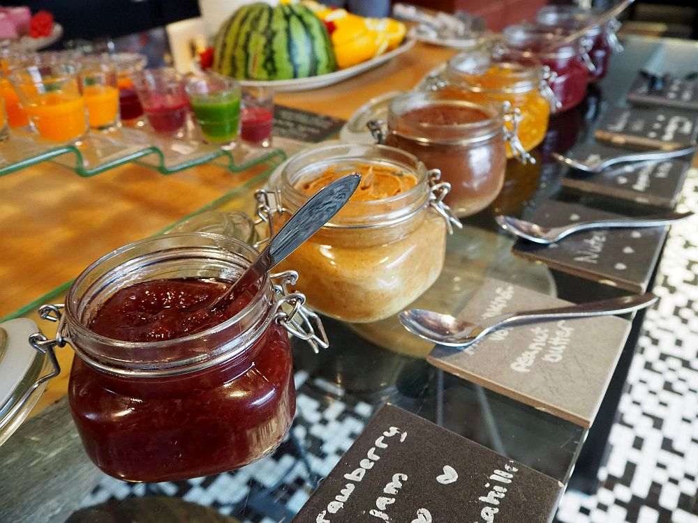 In the foreground, a row of neat containers, each with a spoon and a lable. The nearest says strawberry jam, the second is peanut butter, but there are many more in the row. Behind on a series of small shelves are small glasses of green, red or yellow liquid.