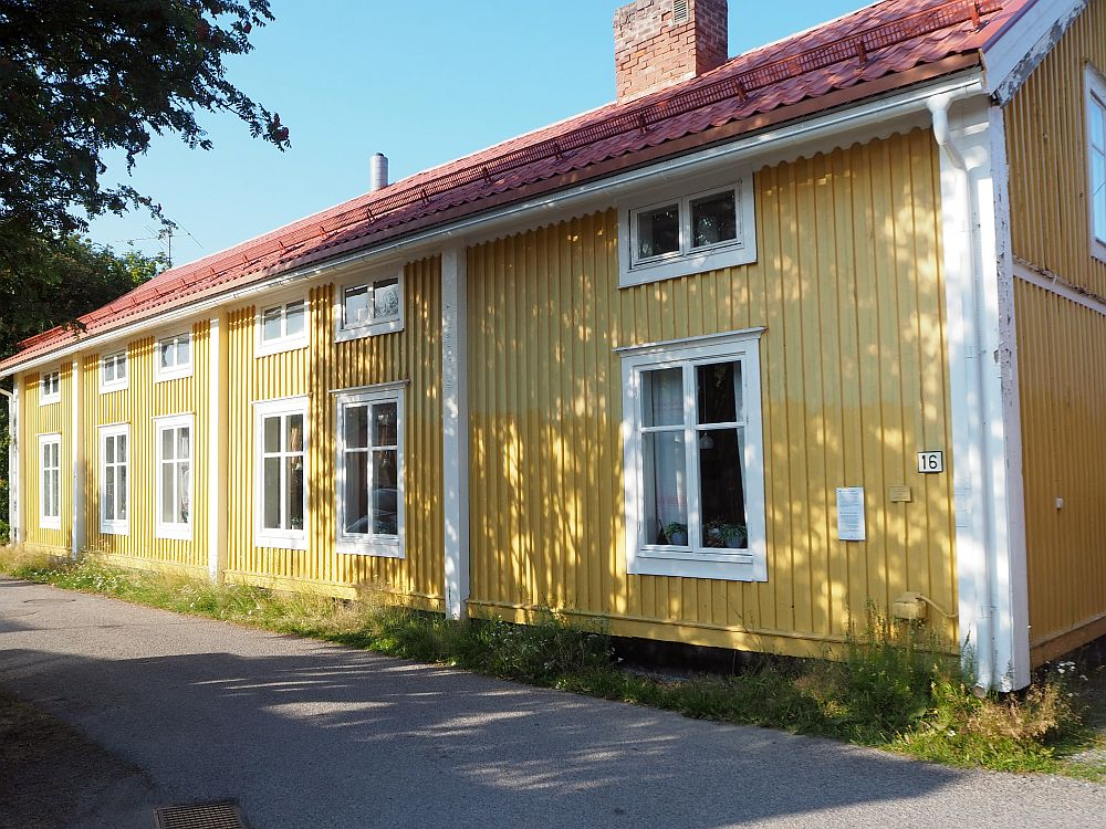This burgher's house in Gammelstad church town is, unlike most, painted yellow, with white trim around the windows and no shutters. It's two stories tall, with tall windows below and smaller, horizontal windows above.