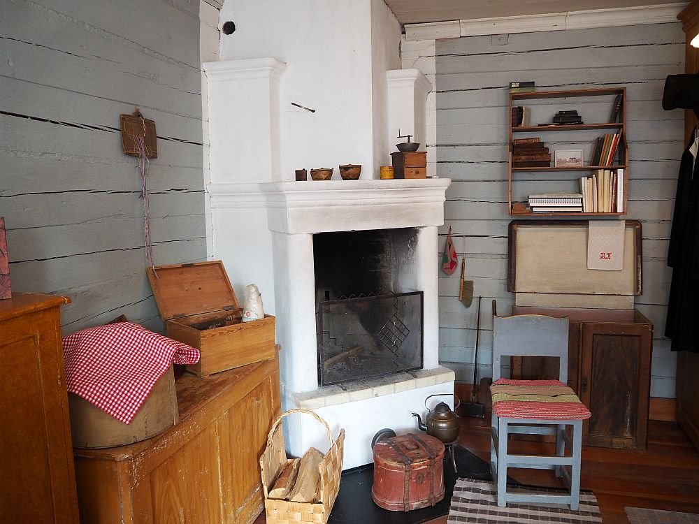 The walls are plain, gray-painted lumber. In the corner is a white painted fireplace. and hearth. On the left is a large chest with a couple of smaller boxes sitting on top of it. In front of the fire is a basket with logs, a round box of some sort, and a tea kettle. Next to the fireplace is a wooden chair with a cushion. Against the wall to the right of the fireplace is another large chest with a small bookshelf mounted on the wall above it.