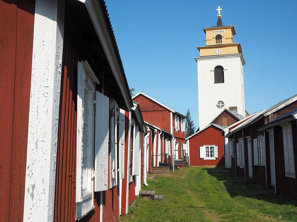A view down a row of houses in Gammelstad church town. They aren't quite lined up and the road curves slightly to the right. At the end is another house, and rising above that is the white bell tower of the church.