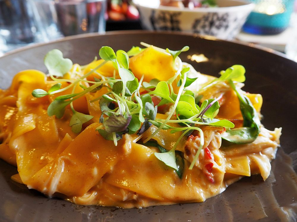 On a dark brown dish, a pile of wide pasta noodles with a creamy sauce and a sprinkling of watercress on top.