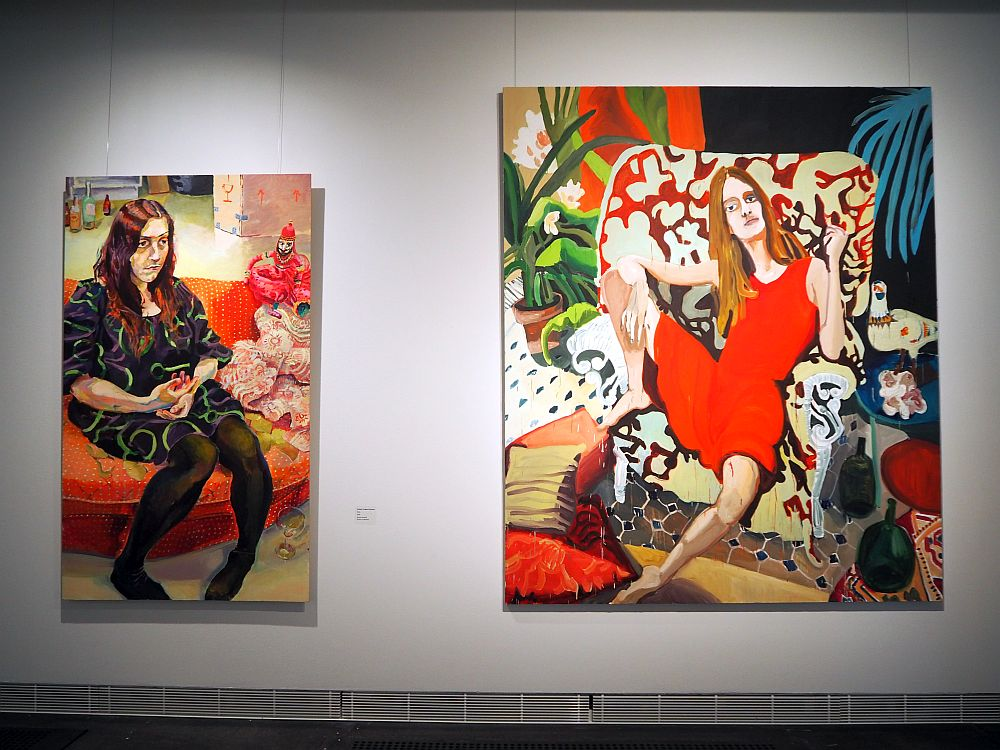 Both paintings show women sitting on chairs. Both are in bright colors and ordinary backgrounds. The woman on the left has long reddish-brown hair, wears a mostly black dress and black tghts, and sits, looking a bit awkward, on a red sofa. She looks to the side. In the Hiltunen painting, the woman looks very relaxed, with one foot up on the big flowered armchair she sits in, her arm leaning on her knee. She has long blond hair and wears a short bright red dress. She stares straight out of the picture, a bold but somewhat bored expression on her face.