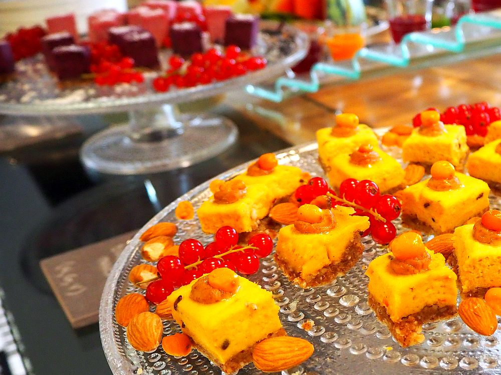 In the foreground, small squares of cake are yellow on what looks like a cookie later. Around them are occasional almonds and redcurrants. In the background, blurry, is another tray with dark brown squares of cake and redcurrants.