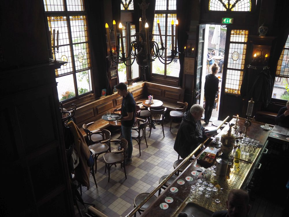 Looking from above down on a small space. Large vertical windows on the left and ahead allow light in. About 3 small round tables are visible with chairs around them and a bench along the left wall. All are brown. the floor is brown tiles. On the right part of the bar is visible with one person sitting on a barstool.