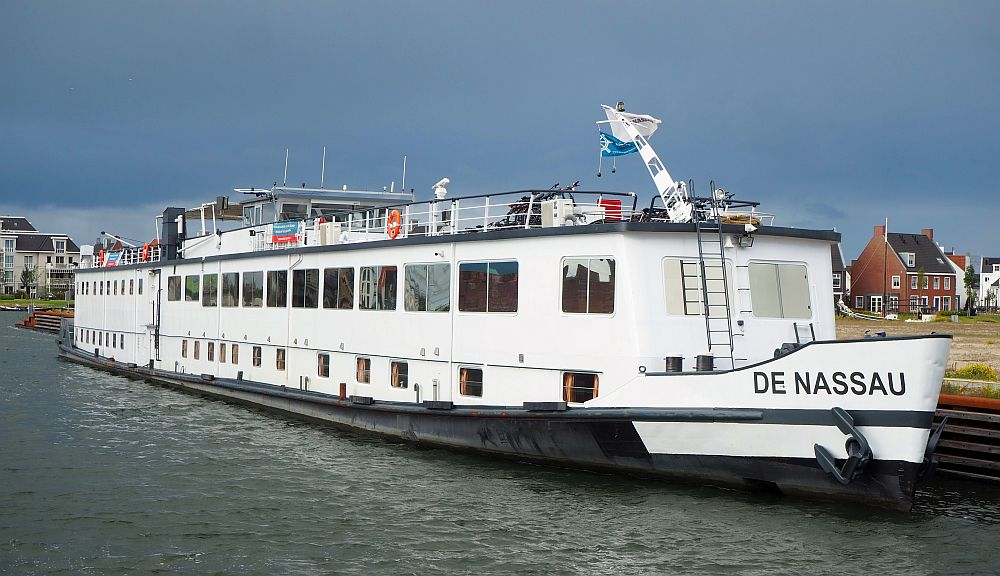 Seen from the front, the boat is very long and narrow, and rides low in the water. Above the black hull, it is white, with a row of small windows below, a row of larger windows above, and a railing around the top deck.
