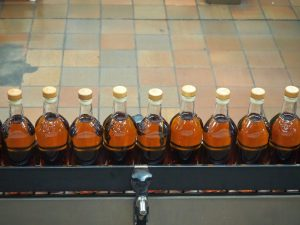 a row of bottles on a conveyer belt. Each holds a golden-brown liquid and has a lid.