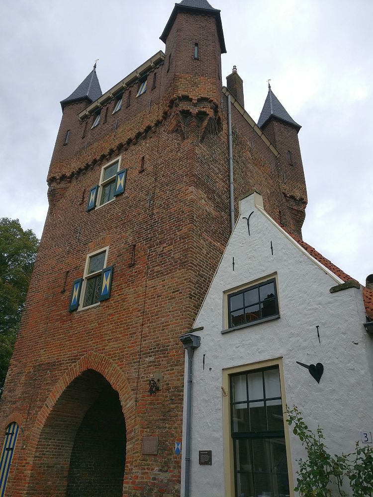The city gate is a tower of red brick, with a small turret on each corner at the top. The small house next to it is simple and white with a peaked roof and two windows.