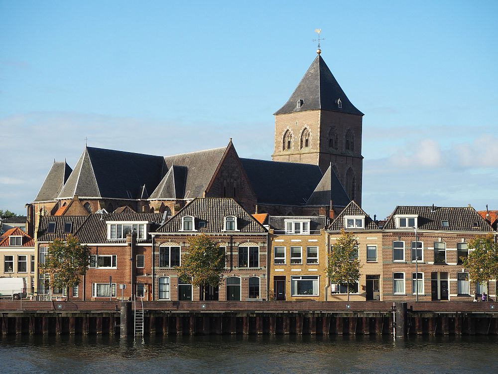 A row of old, square, three-story houses lines the quay with, behind, them, a large, clearly medieval-era church with a blockish square tower that has a pointed roof.