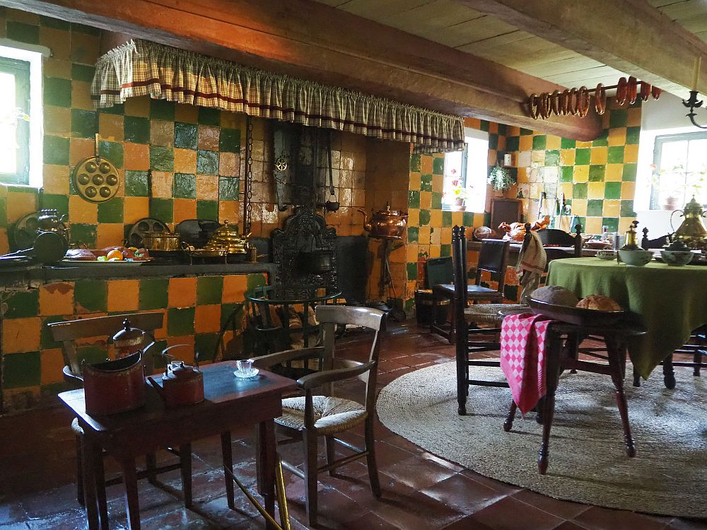 the kitchen's walls are tiled in green and yellow, while the floor is simple dark red tile. In this picture are two tables: on the left is a chld-sized wooden table with two chairs and on the right a regular table with a green tablecloth. Behind is a counter with copper pots and other kitchen items next to a fireplace with an iron stove in it and a door in the wall, presumably for baking. A sort of ruffled curtain hangs around the chimney above. The ceiling is quite low and has heavy beams across it. Sausages hang from a rod between two of the beams.