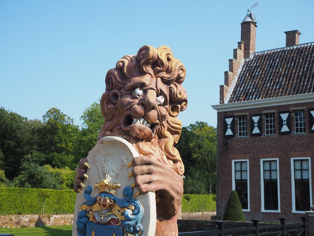 One of the lions at Menkemaborg: he stands upright, clutching a coat of arms in his front claws. He looks to the right, with his eyes looking upward. the lion is painted brown except for the eyes and teeth, which are painted white, and gold claws. The coat of arms is white, with details in gold and blue.