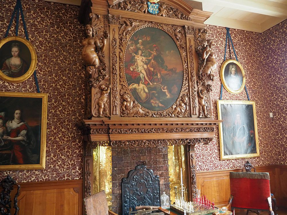 From mantel height to the ceiling, the mantelpiece is carved, with a frilly rim below, naked female figures on the corners, and an ornately-carved oval frame in the middle, framing a scene, probably from classical mythology, invloving a naket woman surrounded by three dressed people, with another naked woman and a baby reclining at her feet.