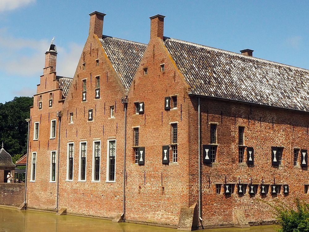 From this view, Menkemaborg looks like 3 row houses together, with three gables on the back of the house. The left-hand one is a tall step gable, while the other two are much simpler pointed gables. All three have what looks like a small chimney at the peak. The windows also vary in size. On the left two parts of the house the ground floor windows are tall and the upper floors are smaller. On the right-hand part (presumably the oldest), all of the windows are small.