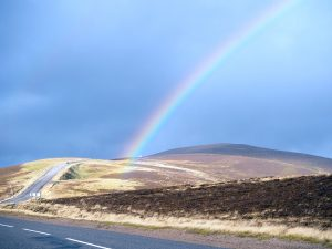 rainbow over a barren, hilly view, with a road winding over the hill into the distance