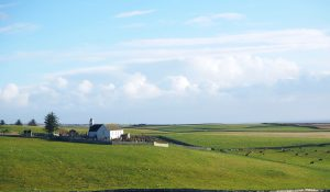 a green, grassy, rolling hills landscape with, on the left, a small church with a wall around the churchyard.