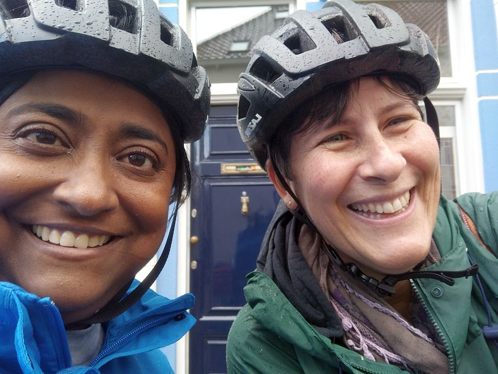 Shobha on the left, looking at the camera, me on the right, looking to the side. Both smiling, wearing black bike helmets and raincoats, which are wet.