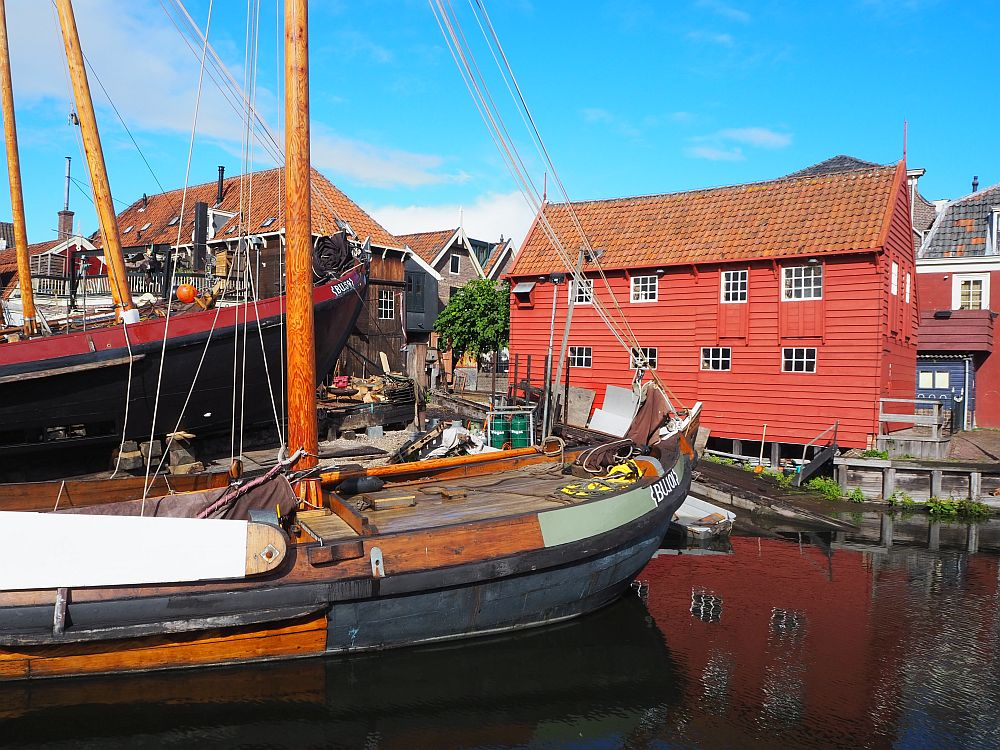 In the foreground a wooden botter lies at anchor. Behind is a bright red building with simple square windows.