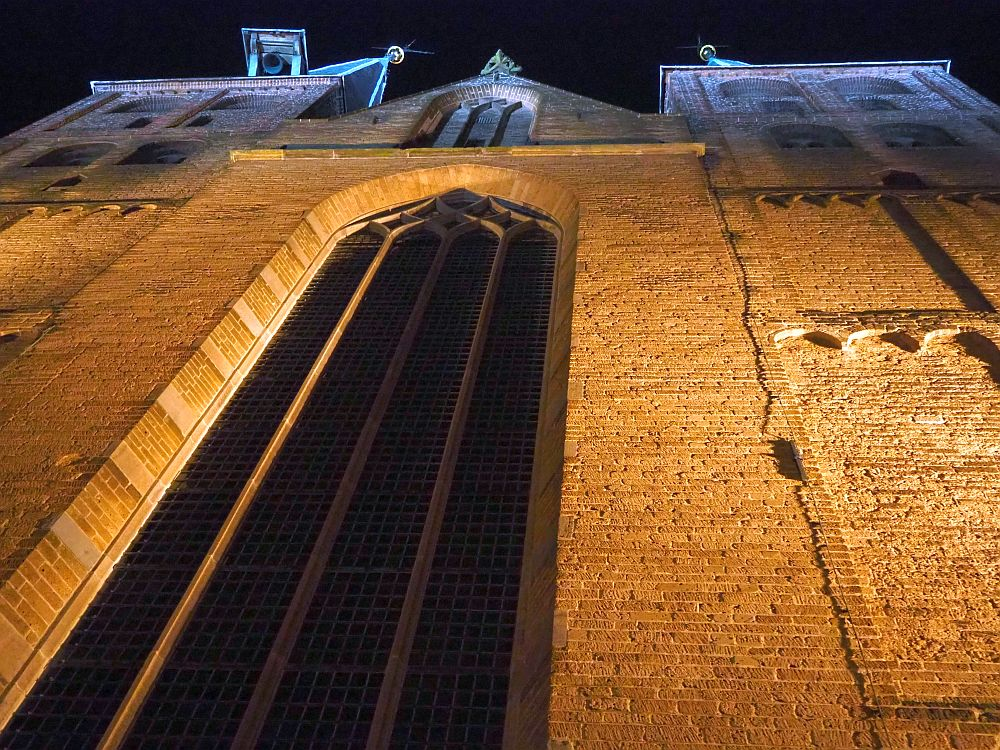 A night view looking straight up the church front: red brick with a tall, gothic window up the center and a peaked roof.