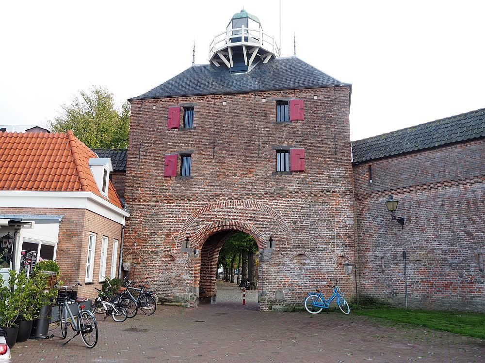 The building is square red brick, with a arched opening through the ground floor and two windows for each of two floors above it. On the top a small round thing protrudes with a round balcony around it: the lighthouse.