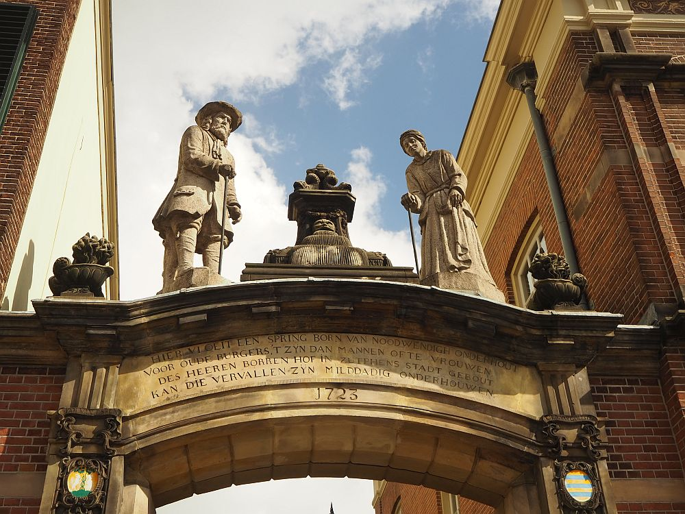 The arch has text carved into it and the date 1723. On top of the arch stand two statues: on the left, a man in jacket and hat, leaning on a cane. On the right, a woman in a long dress, also leaning on a cane.