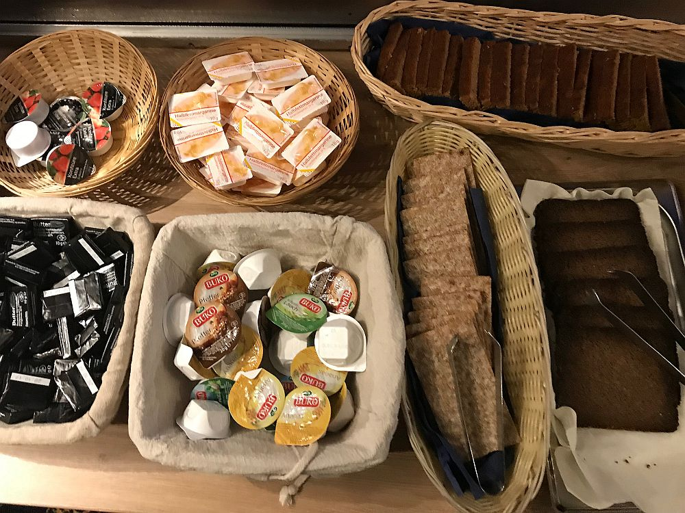 Breakfast on Boat Bike Tours: Baskets each hold a different item: margarine, butter, jam and peanut butter, each in an individual single serving package. Also 3 more baskets holding ontbijktkoek (a sweet spice loaf), roggebrood (a dense thin-sliced pumpernickel) and whole wheat crackers.