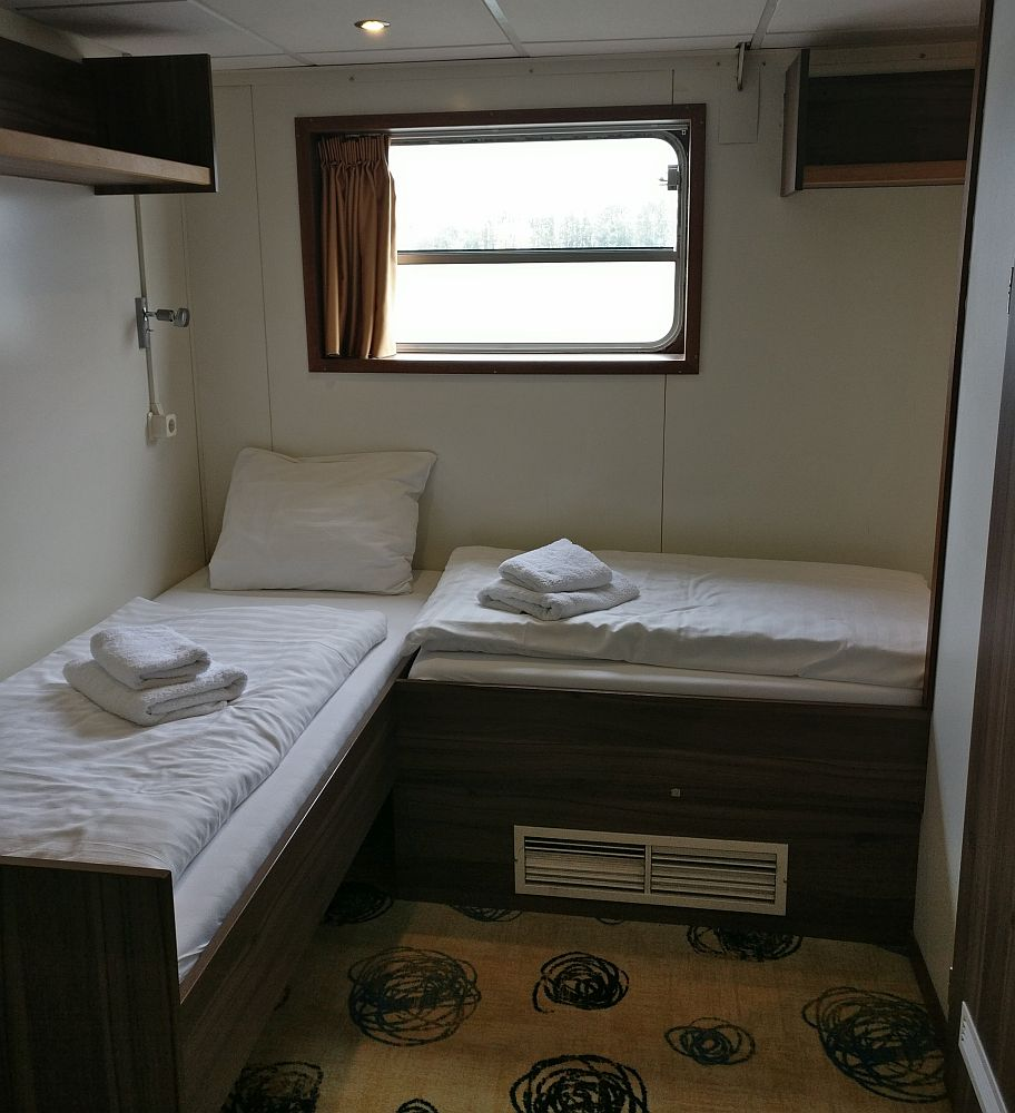 Two twin beds, in our cabin on our Boat Bike Tour, bedding folded on top. A window on the back wall.