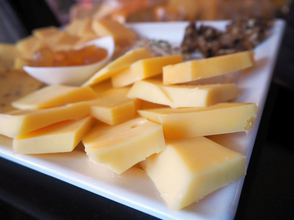 A white plate piled with small squares of cheese: one of the foods we tried on Eating Europe's Jordaan food tour.