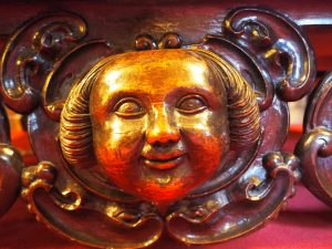 a carved, wooden face glows golden. It is round and smiling, with tight curls on either side.